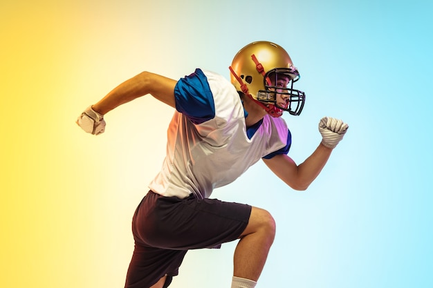 American football player isolated on gradient studio surface in neon light