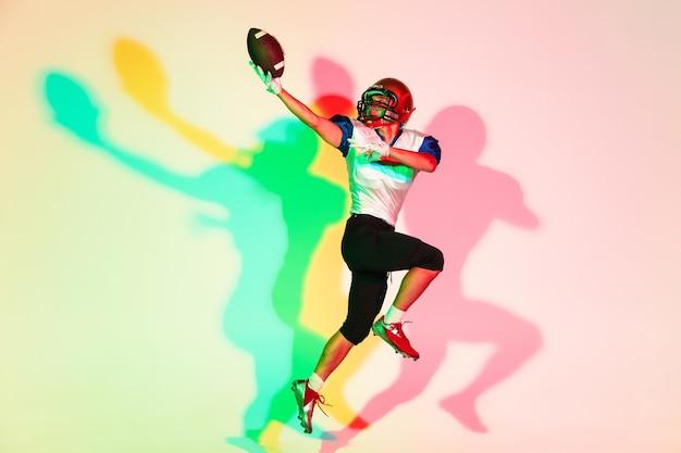 ネオンのグラデーションスタジオの背景にアメリカンフットボール選手
