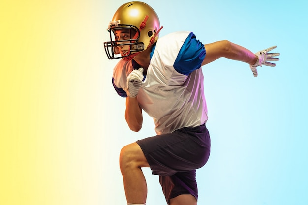 ネオンの光のグラデーションスタジオでアメリカンフットボール選手