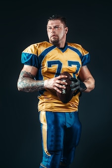 American football player poses with ball in hands