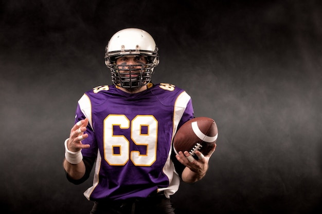 American football player posing with ball on black background
