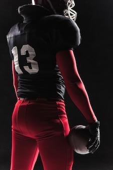 Giocatore di football americano che posa con la palla su spazio nero