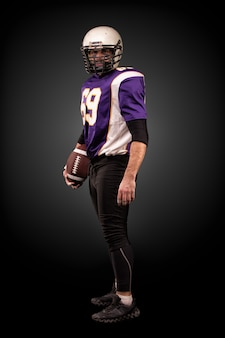 American football player posing with ball on black wall