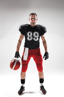 American football player posing with ball on white