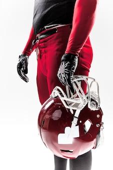 白い背景の上のヘルメットでポーズをとるアメリカンフットボール選手