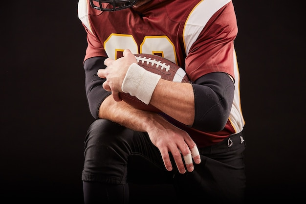 American football player sitting in a position of readiness, hands to keep a mache on a black background, concept