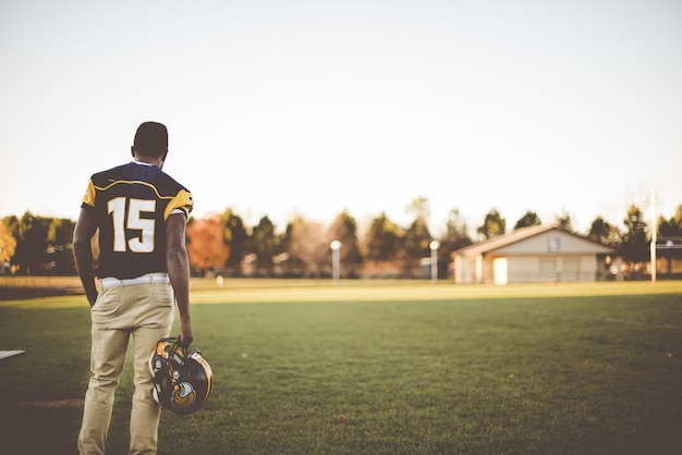 Игрок в американский футбол стоит в поле, готовясь к матчу
