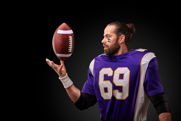 黒い壁にボールを投げるアメリカンフットボール選手