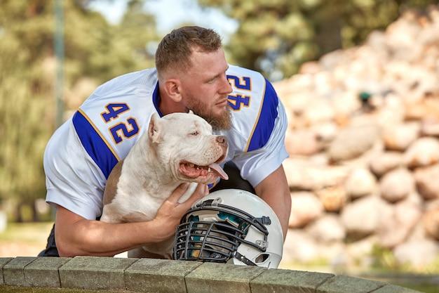 公園でカメラにポーズ犬とアメリカンフットボール選手。 copyspace、スポーツバナー。アメリカンフットボール、動物保護のためのスポーツ。