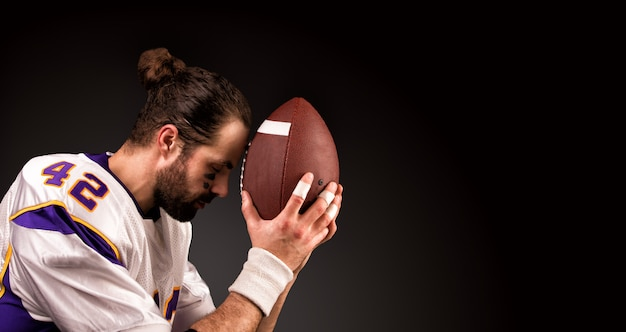 American football player with a ball on moment to pray before the game