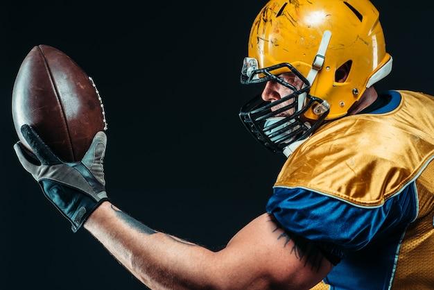 手にひもで締められたボールを持つアメリカンフットボール選手