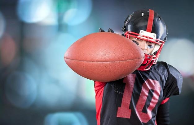 暗い背景に分離されたボールを持つアメリカンフットボール選手