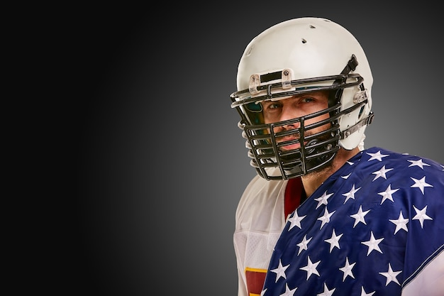 American football player with uniform and american flag proud of his country on a black background.
