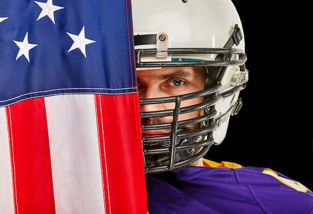 American football player with uniform and american flag proud of his country