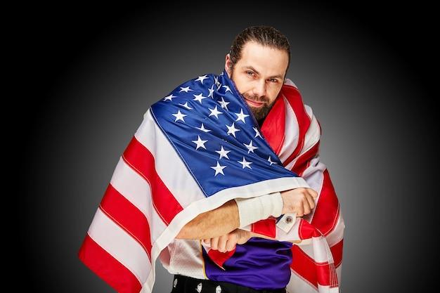 Американский футболист с униформой и американским флагом гордится своей страной на черном фоне.