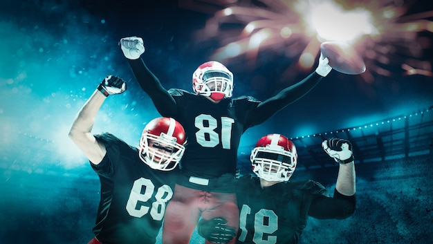 Игроки в американский футбол играют на профессиональном спортивном стадионе. подойдут кавказские мужчины в погонах с мячом. концепция человеческих эмоций и мимики. концепции схватки