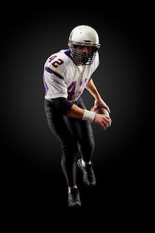 American football sportsman player on black . sport .