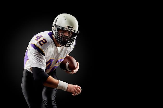 Игрок спорт американского футбола на черноте. спорт