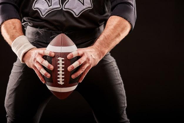 Игрок спортсмена по американскому футболу на стадионе с огнями на черной поверхности, держит мяч перед вами обеими руками