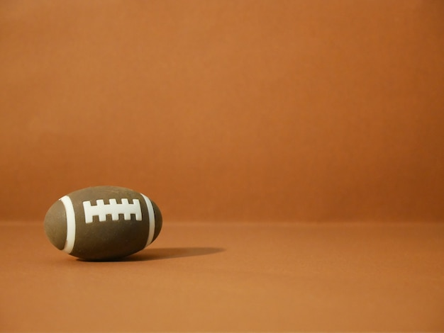 American football with copy space on brown background.
