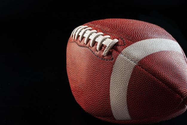暗い背景にアメリカのフットボールのボールをクローズアップ。アメリカンフットボールのコンセプト
