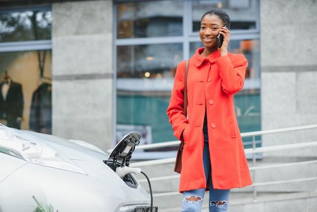 Американская девушка заряжает электроавтомобиль на азс