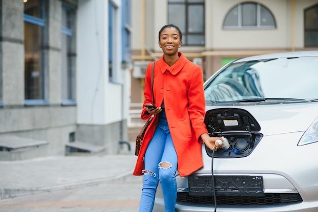 전기 주유소에서 전기 자동차를 충전하는 미국 소녀 프리미엄 사진