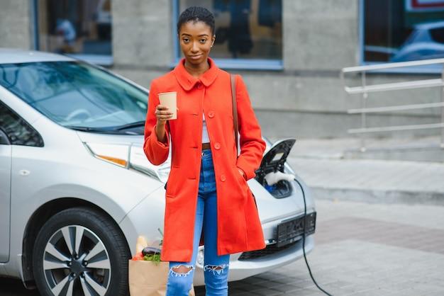 전기 주유소에서 전기 자동차를 충전하는 미국 소녀