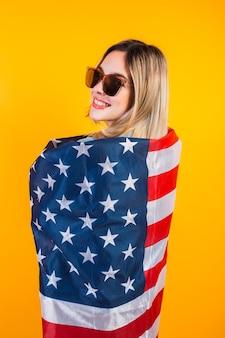アメリカ人の女の子は黄色の背景に大きなアメリカ国旗で身を包みます。