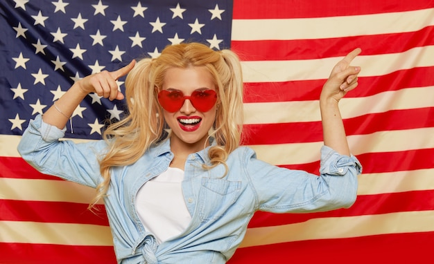 American girl. happy young woman in heart shape sunglasses on usa flag  background. funny and surprised human face. patriotism concept