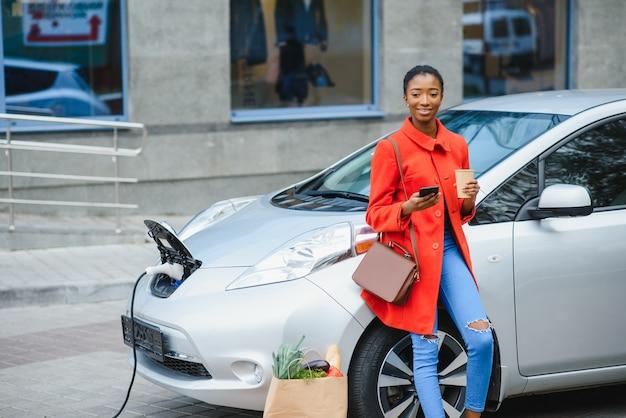 昼間の電気自動車充電ステーションのアメリカ人の女の子。