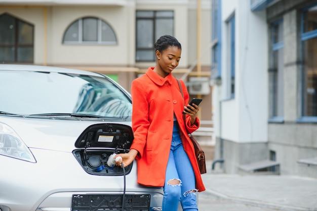 Американская девушка стоит у машины.