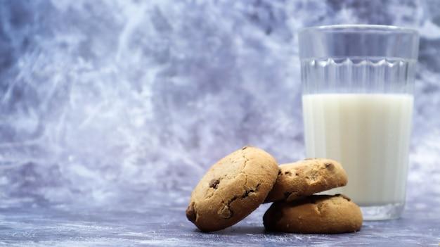 회색 배경에 식물성 우유 한 잔을 곁들인 미국식 글루텐 프리 초콜릿 칩 쿠키. 초코칩 쿠키. 달콤한 파이, 디저트. 요리 배경입니다. 공간을 복사합니다.
