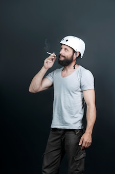 American handsome bearded man in a bicycle helmet. stop smoking. russian man smoking cigarette after intense biking training. sport and harmful habit. active person enjoying everyday life moments