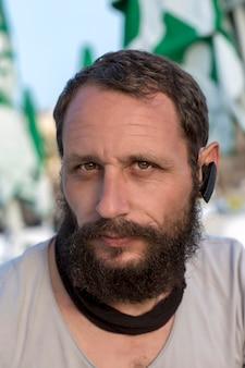 Американский красивый бородатый мужчина в беспроводном наушнике. концепция удобство беспроводных наушников. задумчивый серьезный русский мужчина смотрит в камеру, используя громкую связь, чтобы говорить по телефону