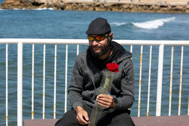 American handsome bearded man wearing sunglasses, cap and hood jacket against blue sky. portrait of russian caucasian brutal dude holding a red rose flower in hand. romantic and valentines day holiday