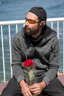 American handsome bearded man wearing sunglasses, cap, hood jacket with rose waiting his woman on the sea beach. russian caucasian brutal fashion male looks to side, relaxed pose with natural face