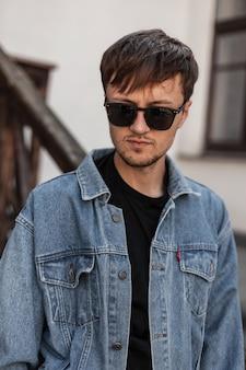 Американский красивый молодой человек с бородой в модных солнцезащитных очках, в стильной синей джинсовой куртке и футболке стоит на улице возле старинного здания в весенний день. привлекательный хипстерский парень.