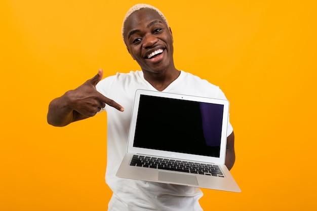 白いtシャツを着たアメリカ人は、オレンジ色の背景にモックアップ付きのラップトップディスプレイを示しています
