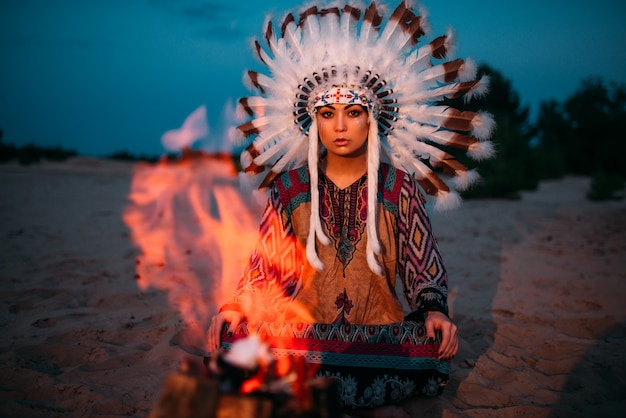 American indian girl against bonfire in the night, female shaman, cherokee, navajo. headdress made of feathers of wild birds. traditional ritual