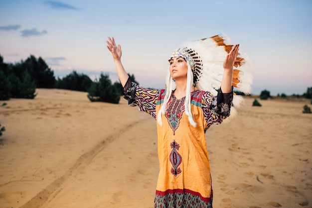 American indian woman hands up, ritual, ritualistic ceremony cherokee, navajo reservation people. headdress made of feathers of wild birds