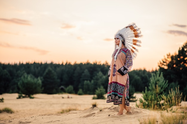 アメリカインディアンの女性は、屋外で遠くを見ています。チェロキー、ナバホ文化。野鳥の羽でできた頭飾り。伝統的な衣装