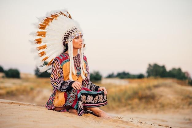 ヨガのポーズで座っているアメリカインディアンの女性。野鳥の羽でできた頭飾り。チェロキー、ナバホ文化、民族の伝統
