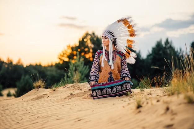 ヨガのポーズで座っているアメリカインディアンの女性