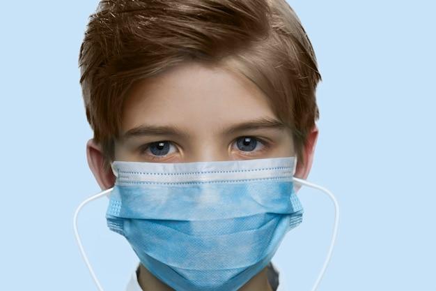 마스크를 쓴 미국 소년은 바이러스로부터 자신을 보호합니다.