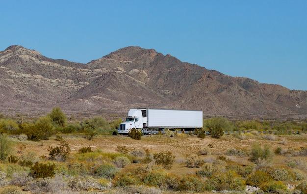 미국은 산 고속도로에서 냉동차를 빠르게 운반하는 대형 장비 세미 트럭을 만듭니다.