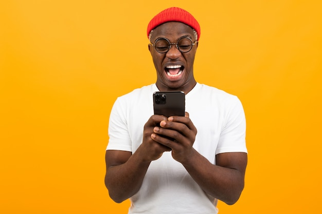 American man is very surprised looking at the screen of his smartphone