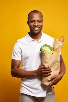 Американский мужчина стоит с бумажный мешок свежих продуктов.