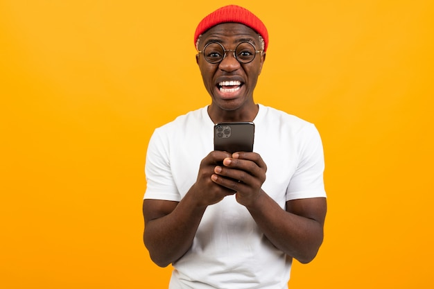 American man very surprised holding a smartphone in his hands on yellow with copy space