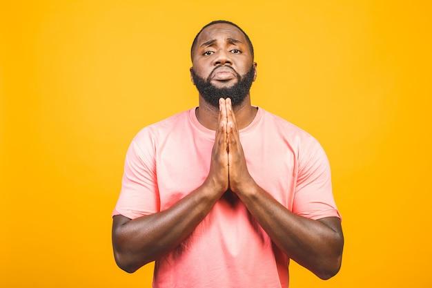 Американский человек с афро волосами носить случайный стоя над изолированной желтой стеной, прося и молясь руками вместе с выражением надежды на лице очень эмоциональный и обеспокоенный.